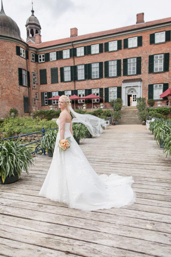 Braut mit Blumen in der Hand steht seitwärts vor einem Schloss. Die Schleppe des Kleides ist ausgebreitet, der Schleier flattert im Wind.